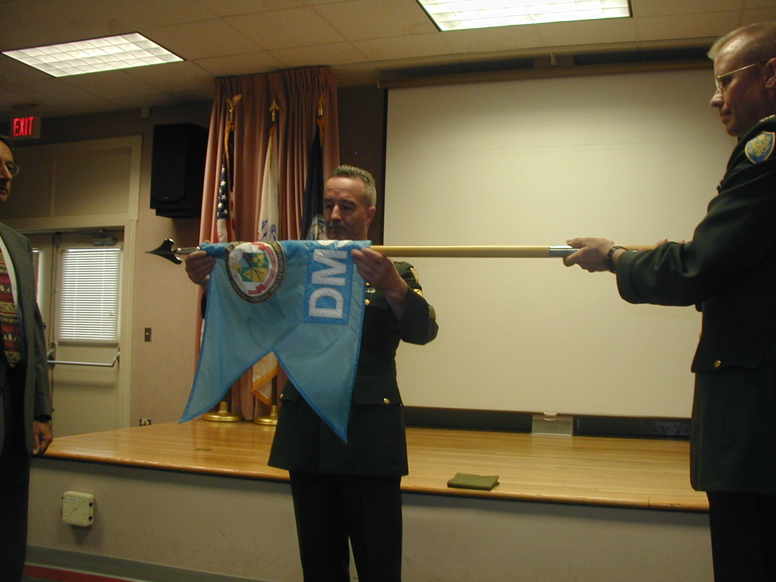 The casing of the DMS flag with COL Robert Slusar on the right, SGM Paul Swartz and Mr Dave Broadhurst College (NGC) Dean